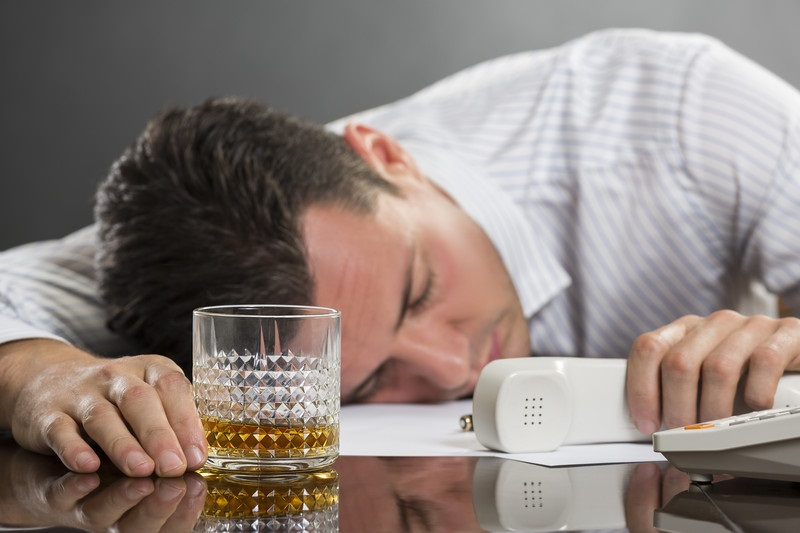 Addicted man passed out at his desk with a glass of alcohol in front of him